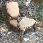 Discarded armchair with thoroughly read booknect to railroad on Mondo Beach