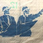 Stencil in blue of to contractors with hard hats.